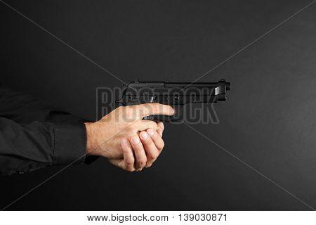 Man's hands holding gun on black background