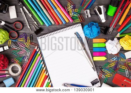 Bunch of office supplies on wooden desk with notepad for text