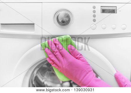 Female hands in gloves washing washing machine. Close-up.
