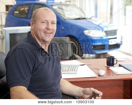Car salesman sitting in showroom smiling