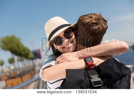 My darling. Pleasant cheerful beautiful woman smiling and embracing with her boyfriend while standing outdoors