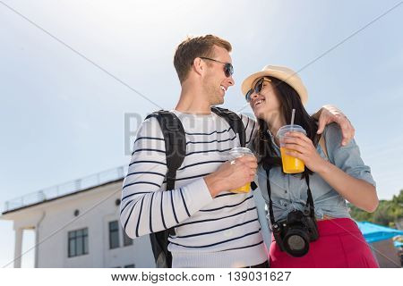 Brighten up your day. Cheerful content smiling couple bonding to each other and drinking juice while having a walk