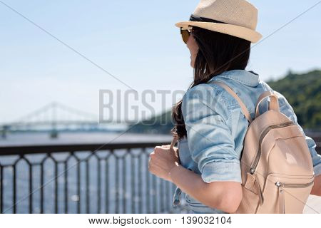 Romantic scenery. Pleasant delighted nice woman holding her bag and looking on the river while enjoying landscape