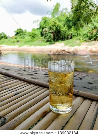 Glass of beer with ice on Thai style bamboo table with natural background.
