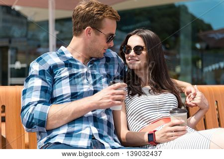 Nice time together. Positive relaxed smiling couple sitting on the bench and drinking coffee while resting together