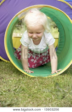 Young Girl Crawling Through Play Equipment