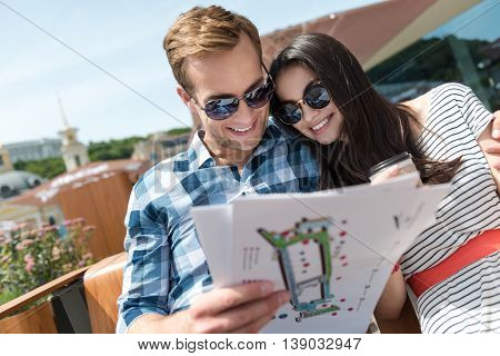 Modern citizens. Cheerful delighted smiling couple sitting on the bench and holding city man while resting together