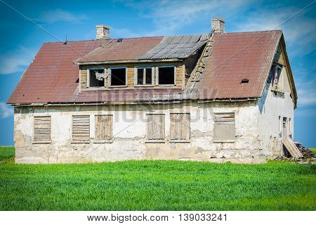 Old abandoned damaged house on grass field