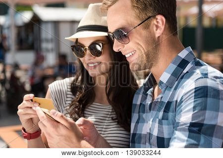 In a good mood. Cheerful delighted smiling couple holding credit card and sitting on the bench while resting together