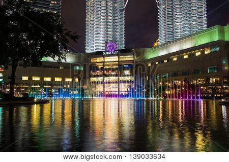 KUALA LUMPUR MALAYSIA - FEBRUARY 29: Colorful rainbow fountain show in park nearby Suria KLCC Mall on February 29 2016 in Kuala Lumpur Malaysia. Suria KLCC is one of the premier shopping mall in Malaysia.