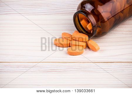 Orange pills in dark brown glass container on light wooden table