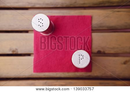 Top view of salt and pepper metall bottles on red napkin on wooden table