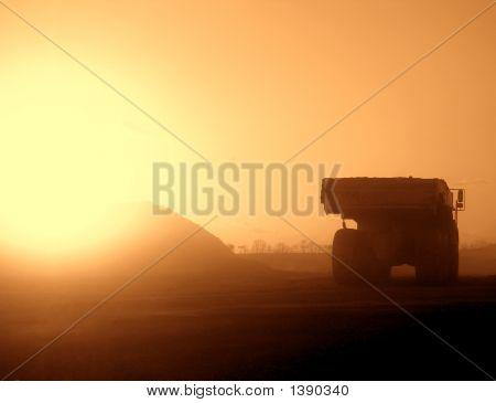 Caminhão em um local de construção empoeirados ao pôr do sol