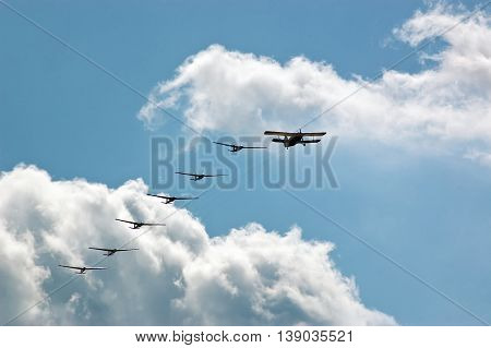 Silhouette sport aircraft with propeller and gliders plane pulling a six gliders against the clouds in the air show performance.