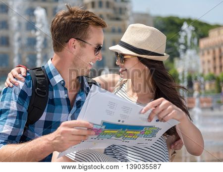 Travel together. Pleasant loving smiling couple holding city map and sitting near fountain while looking at each other