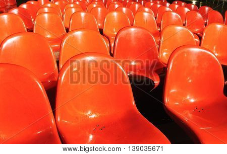 Wet red plastic chairs in stadium or theatre