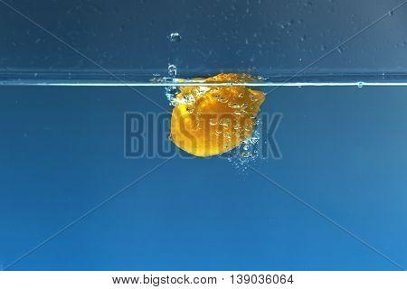 Fresh juicy lemon falling in water on dark background