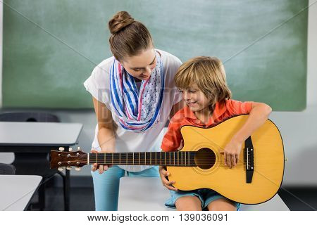 Teacher assisting boy to play guitar in classroom