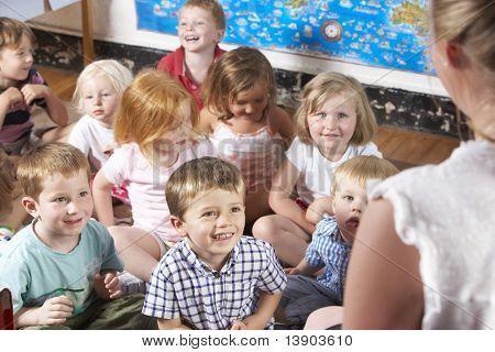 Clase de Montessori/Pre-escolar que escuchar al maestro en alfombra