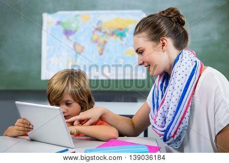 Smiling teacher assisting boy using digital tablet in classroom