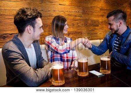 Happy friends shaking hands at restaurant