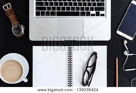 Creative flat lay photo of workspace desk with laptopGlasses smart phone with ear phone wacth coffee and blank notebook with copy space background minimal style isolate black background