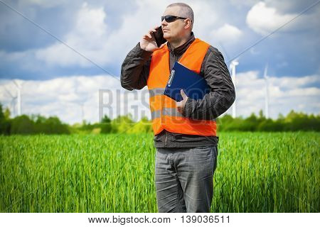 Farmer with smartphone on the green cereal field
