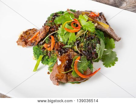 Chinese sichuan meat with broccoli served on a white plate