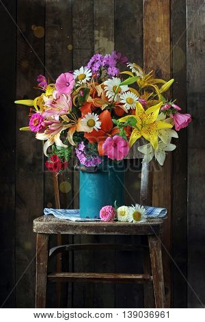 Still life with a bouquet of garden flowers in a blue jug on a chair against the wall of planks in a rustic style.