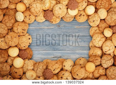 Cookies and sweet biscuits frame at blue wood background with copy space. Oatmeal and chocolate drops cookies border. Dessert on wooden table top view