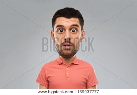 emotion, facial expressions and people concept - surprised man in polo shirt over gray background (funny cartoon style character with big head)