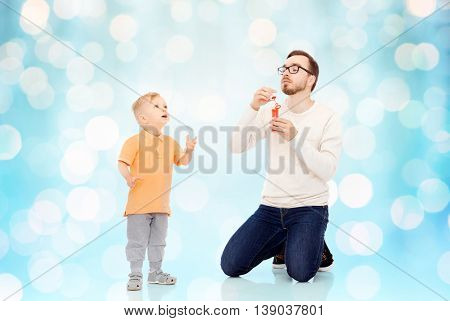 family, childhood, fatherhood, leisure and people concept - happy father and little son blowing bubbles and having fun over blue holidays lights background