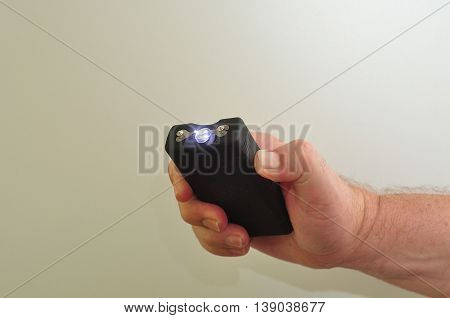 A taser held in a mans hand isolated on a white background