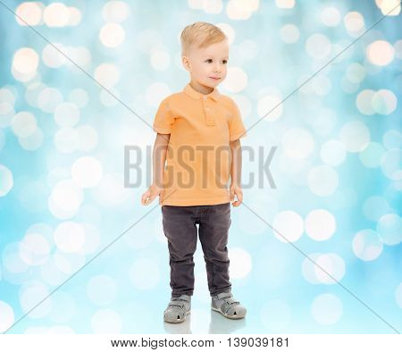childhood, fashion and people concept - happy little boy in casual clothes over blue holidays lights background
