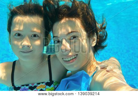 Children swim in pool underwater, making selfie, happy active girls have fun, kids sport on family vacation