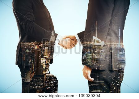 Businessmen shaking hands on blue city background. Double exposure