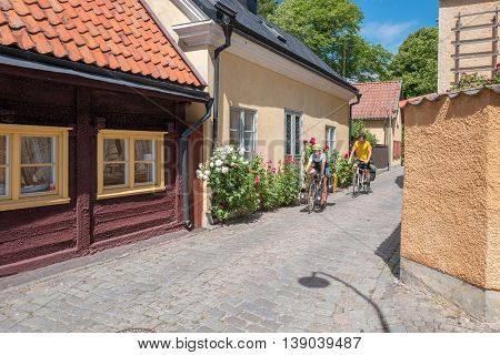 VISBY, SWEDEN - JULY 8, 2016: Tourists on bikes explore medieval Visby. Visby is a historic Hanse town and a major tourist destination on Swedish Baltic sea island Gotland.