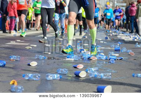 Marathon running race, runners feet and plastic water cups on road near refreshment point, sport, fitness and healthy lifestyle concept