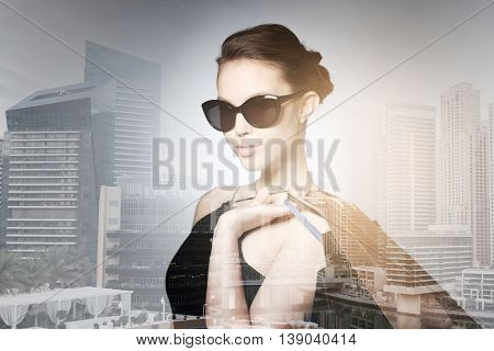sale, fashion, people and luxury concept - happy beautiful young woman in black sunglasses with shopping bags over dubai city with double exposure background