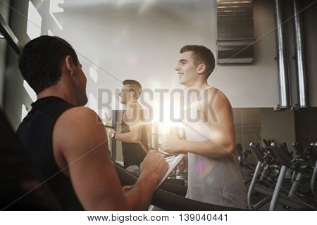 sport, fitness, lifestyle, technology and people concept - men with personal trainer exercising on treadmill in gym