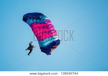 Skydiver On Colorful Parachute In Blue Clear Sky. Active Lifestyle Extreme Hobbies