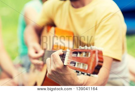 music, leisure and people concept - close up of man playing guitar at camping