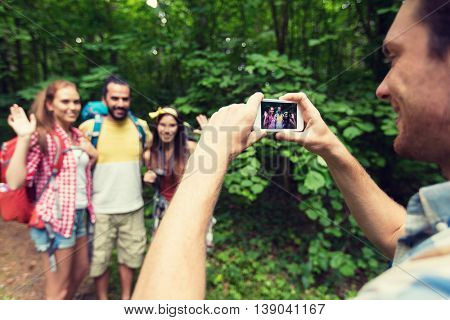 travel, tourism, hike, technology and people concept - close up of happy young man photographing friends with backpacks by smartphone outdoors