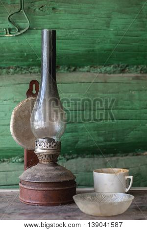 Old dirty kerosene lamp on a dusty table
