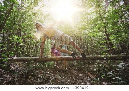 adventure, travel, tourism, hike and people concept - group of smiling friends walking with backpacks and jumping over fallen tree trunk in woods