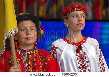 ROMANIA TIMISOARA - JULY 92016:Young Ukrainian in traditional costume with national flag present at the folk festival