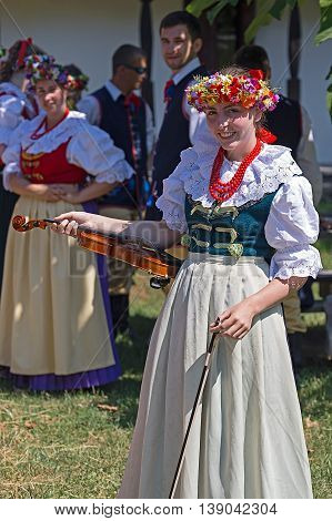 ROMANIA TIMISOARA - JULY 102016: Young singer girl at violin from Poland in traditional costume present at the folk festival