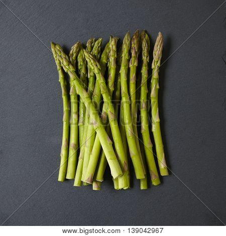 A pile of asparagus spears on a rustic slate background