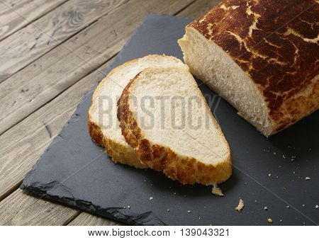 A loaf and slices of crusty white bread on a rustic slate chopping board and wooden table top background