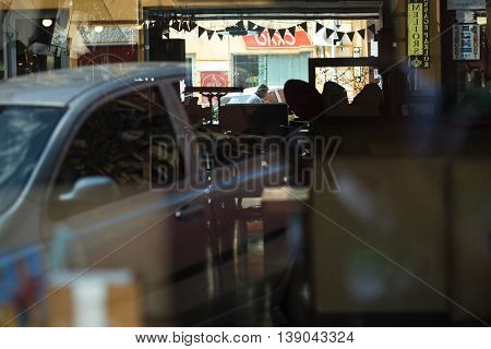 Kiev, Ukraine, 16 July 2016. Showcase of urban сafé in the Kiev. The young man reflected in the mirror of the cafe. Man sitting outdoors and drinking coffee. The car and interior of the cafe are reflected in glass of showcases.